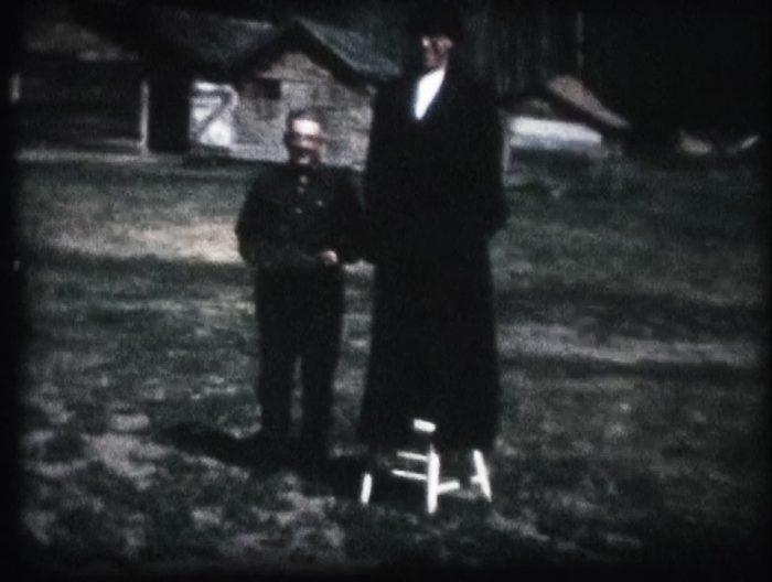 Capture d'image d'un film Super 8 d'Alcide Short filmé chez Georgiana Beaupré et Joe Short à Park Valley, SK. Sur la photo, un homme porte le manteau énorme d'Edouard et l'autre tient sa grande chaussure.